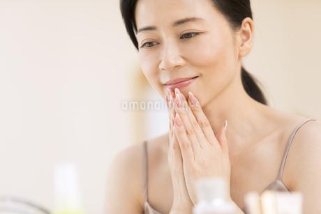 顎に両手を添えて微笑む女性の写真素材 [FYI02968854]