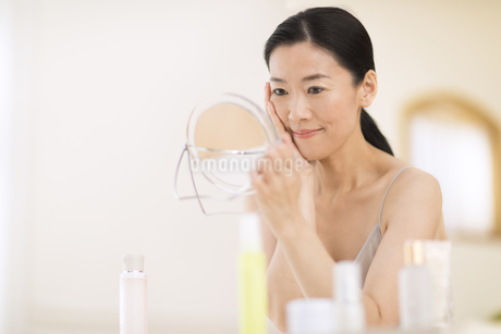 鏡の前でスキンケアをする女性の写真素材 [FYI02968856]
