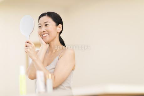 鏡の前でスキンケアをする女性の写真素材 [FYI02968857]