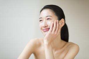 頬に片手を添えて微笑む女性の写真素材 [FYI02968865]