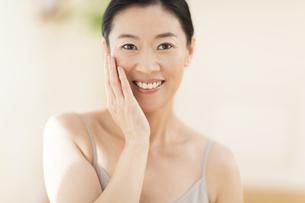 頬に片手を添えて微笑む女性の写真素材 [FYI02968867]