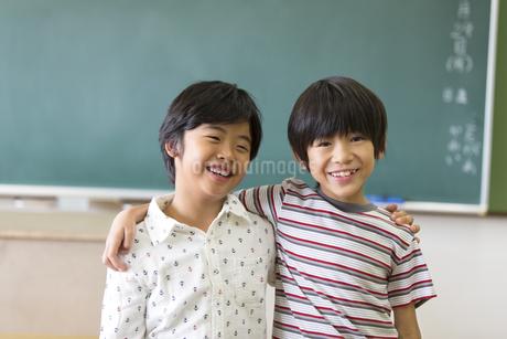 黒板の前で肩を組んで笑う男の子2人の写真素材 [FYI02968876]