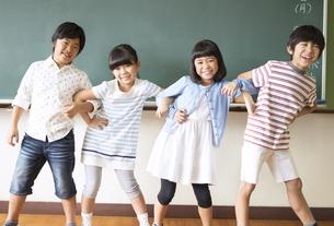 黒板の前で腕を組んで笑う子供たちの写真素材 [FYI02968877]
