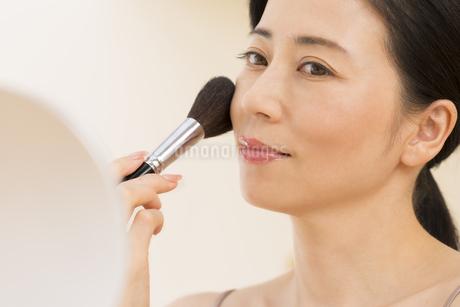 チークブラシを顔にあてる女性の写真素材 [FYI02968881]