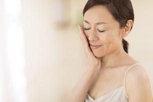 頬に片手を添えて目を瞑り微笑む女性の写真素材 [FYI02968886]