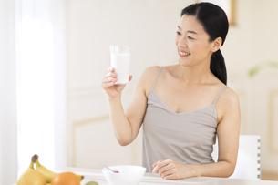 牛乳を手に微笑む女性の写真素材 [FYI02968888]