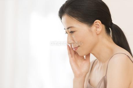 頬に片手を添える女性の横顔の写真素材 [FYI02968889]