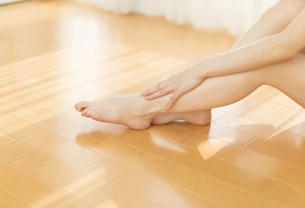 脚のマッサージをする女性の脚元の写真素材 [FYI02968890]