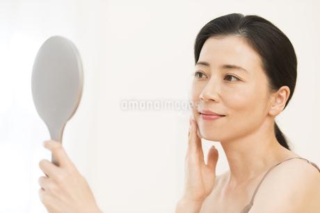 頬にコットンをあてスキンケアをする女性の写真素材 [FYI02968895]