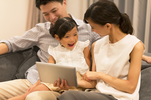 ソファーでタブレットPCを見る家族の写真素材 [FYI02968897]
