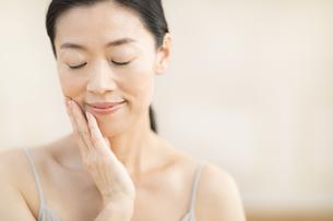 頬に片手を添えて目を瞑る女性の写真素材 [FYI02968910]