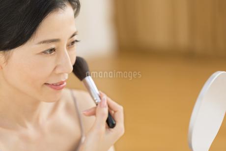 チークブラシを顔にあてる女性の写真素材 [FYI02968917]