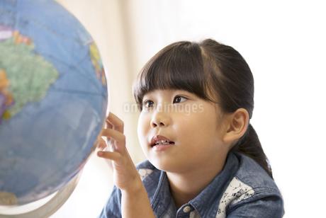 教室で地球儀を見る女の子の写真素材 [FYI02968918]