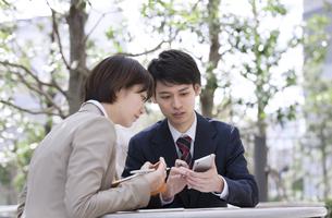 スマートフォンを見るビジネス男女の写真素材 [FYI02968923]