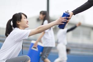 ドリンクボトルを手渡す女子マネージャーの写真素材 [FYI02968926]
