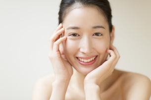 頬に両手を添えて微笑む女性の写真素材 [FYI02968931]