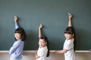 黒板の前で振り返る女の子3人の写真素材 [FYI02968933]