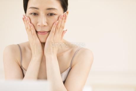 鏡の前でスキンケアをする女性の写真素材 [FYI02968940]