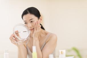 鏡の前でスキンケアをする女性の写真素材 [FYI02968944]