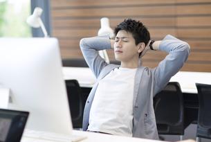 PCの前の目を閉じるビジネス男性の写真素材 [FYI02968945]