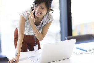 横を向いて電話するビジネス女性の写真素材 [FYI02968946]