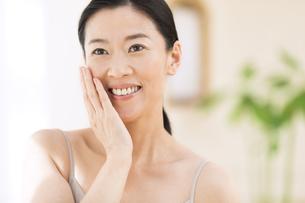 頬に片手を添えて微笑む女性の写真素材 [FYI02968947]