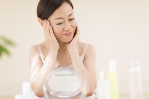 鏡の前でスキンケアをする女性の写真素材 [FYI02968948]