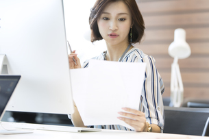 PCの前で資料を見るビジネス女性の写真素材 [FYI02968951]