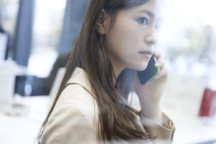スマートフォンで通話するビジネス女性の写真素材 [FYI02968954]