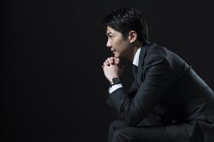 椅子に座り考え込むビジネス男性の横顔の写真素材 [FYI02968955]