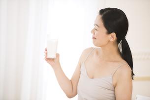 牛乳を手に微笑む女性の写真素材 [FYI02968956]