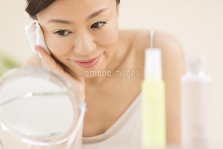 頬にコットンをあてスキンケアをする女性の写真素材 [FYI02968958]