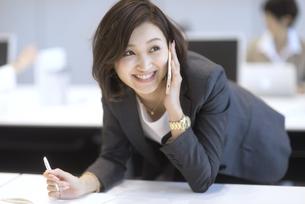 デスクに前のめりで通話するビジネス女性の写真素材 [FYI02968965]