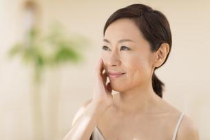 頬に片手を添えて微笑む女性の写真素材 [FYI02968967]