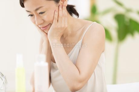 鏡の前でスキンケアをする女性の写真素材 [FYI02968970]