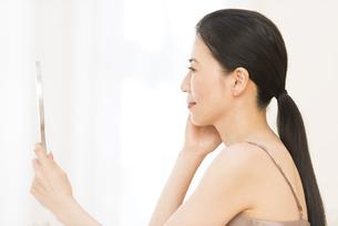 手鏡を見る女性の横顔の写真素材 [FYI02968976]