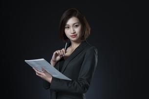 資料とペンを手に持つビジネス女性の写真素材 [FYI02968977]