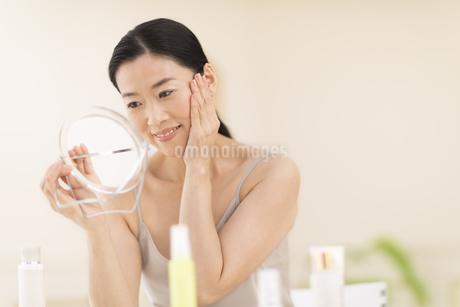 鏡の前でスキンケアをする女性の写真素材 [FYI02968980]