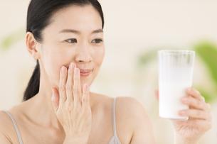 牛乳を手に微笑む女性の写真素材 [FYI02968984]