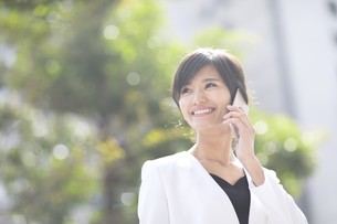 スマートフォンで通話するビジネス女性の写真素材 [FYI02968992]