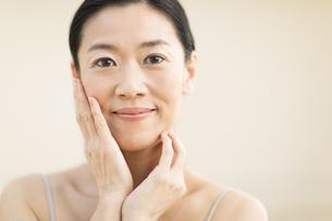頬に両手を添えて微笑む女性の写真素材 [FYI02968993]