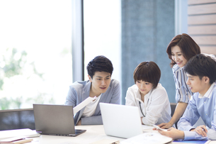 PCを見る男女4人のビジネスマンの写真素材 [FYI02968996]