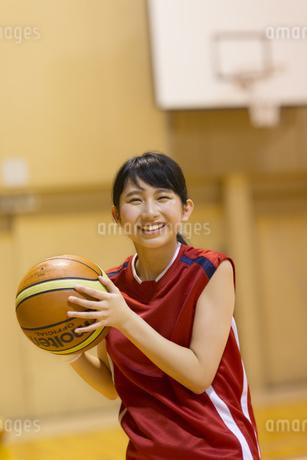 バスケットボールを持って笑う女子学生の写真素材 [FYI02968997]