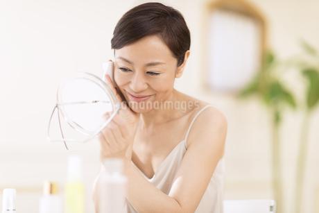 鏡の前でスキンケアをする女性の写真素材 [FYI02968999]