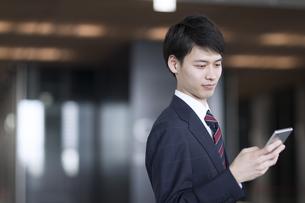 スマートフォンを操作するビジネス男性の写真素材 [FYI02969000]
