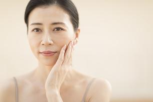 頬に片手を添える女性の写真素材 [FYI02969002]