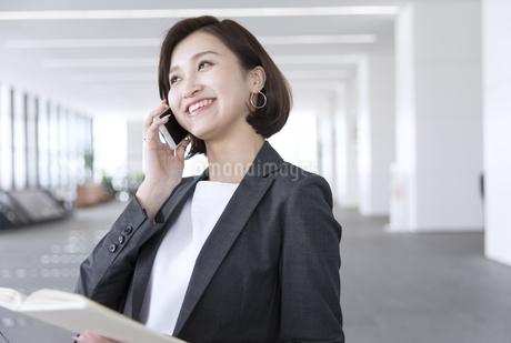 手帳を持ちスマートフォンで通話するビジネス女性の写真素材 [FYI02969003]