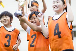 優勝カップを持って喜ぶ子供たちの写真素材 [FYI02969005]