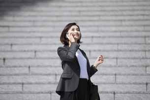 スマートフォンで通話するビジネス女性の写真素材 [FYI02969007]