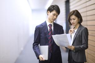 オフィスの廊下で打ち合わせをするビジネス男女の写真素材 [FYI02969008]